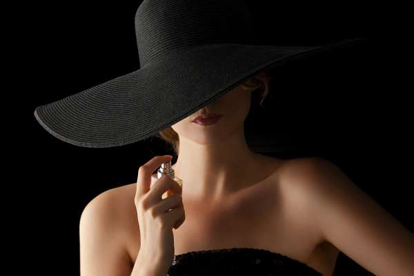 Chic woman with fragrance in her hand