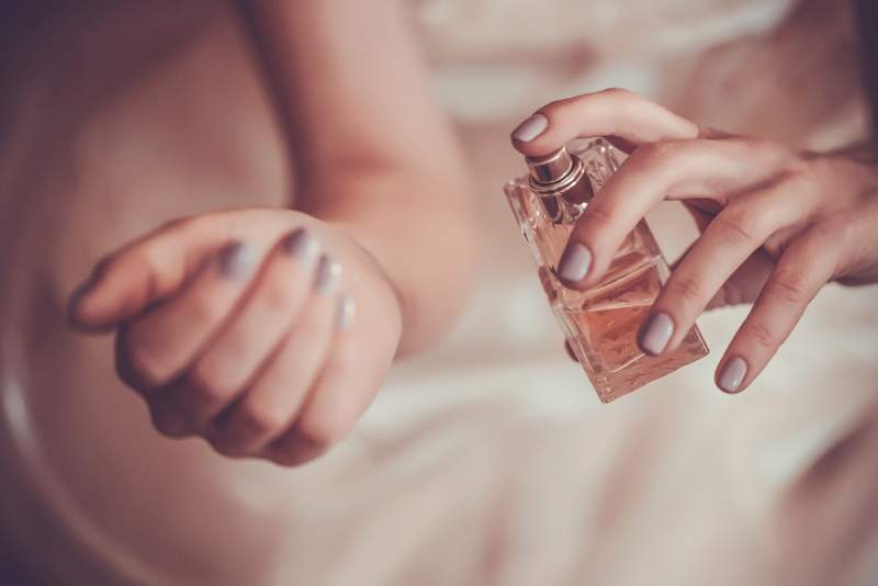 Woman applying fragrance to wrist
