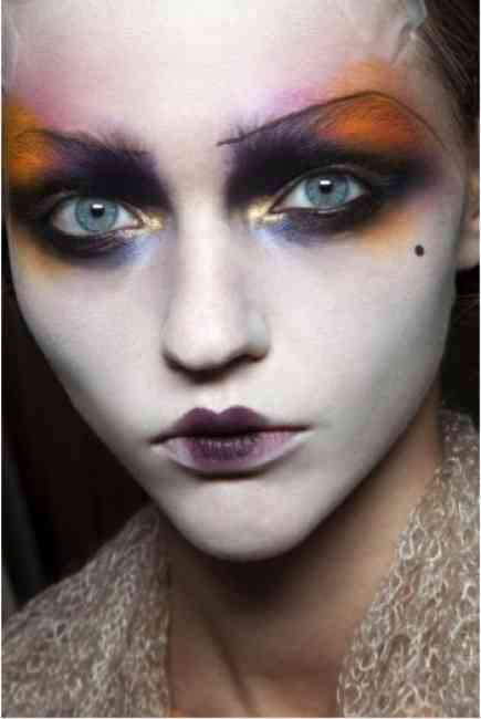 Model wears dramatic and colourful makeup on the eyes, a unique approach to standard beauty looks.
