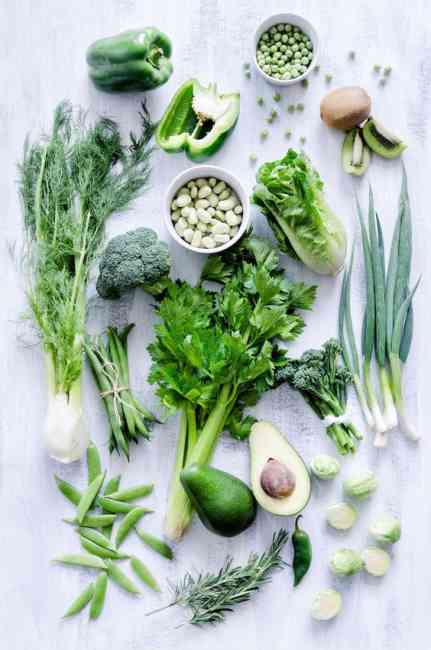 Flat lay of green vegetables e.g. Capsicum, celery, peas, avocado, lettuce, rosemary, broccolini, Brussels sprouts etc.