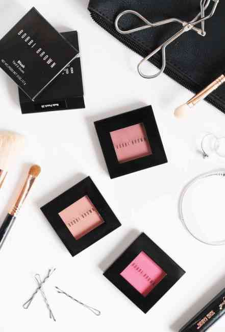 Flat lay of Bobbi Brown Cosmetics blush products, makeup brushes, makeup bag, bobby pins.