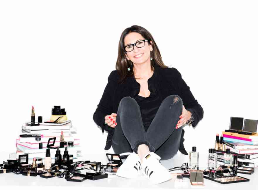 Bobbi Brown sitting on the floor surrounded by her makeup products and the books she has written.