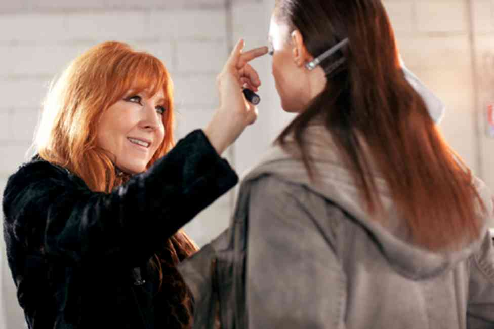 Charlotte Tilbury applying eye makeup to a model behind the scenes of a fashion shoot.