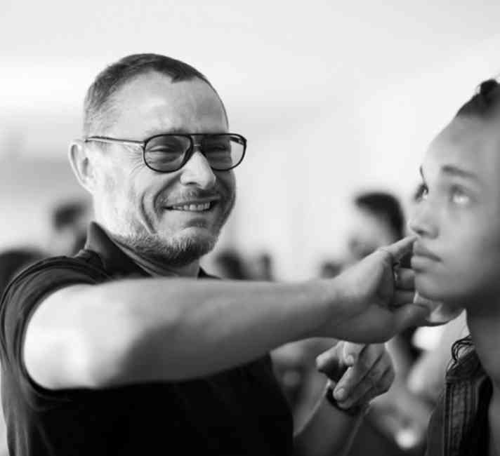 Black and white image of a smiling Tom Pecheux applying makeup to model.