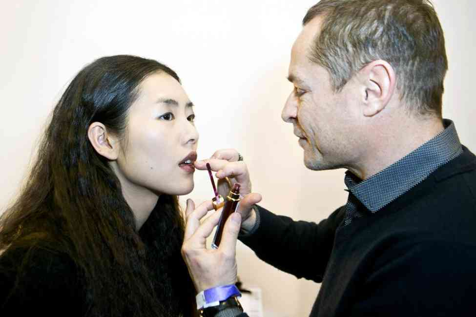 Tom Pecheux applying a lip product to model in a non-conventional way, e.g. with his fingers