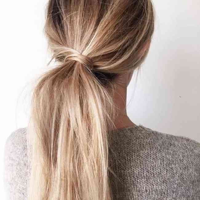 Blonde low ponytail with hair wrapped around the hair elastic.