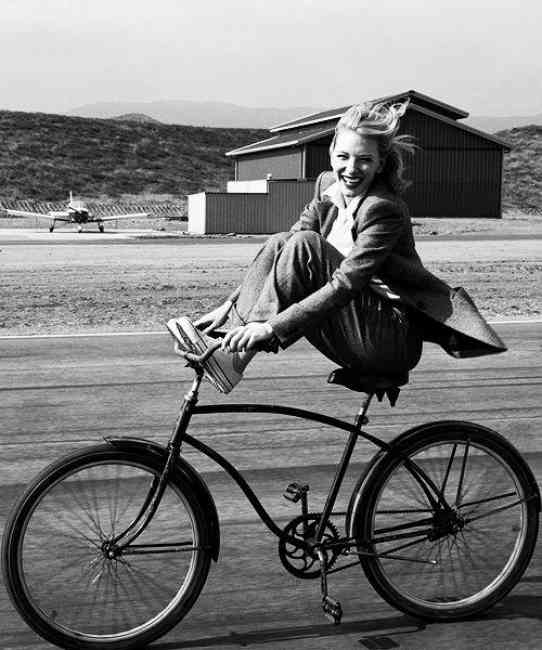 Black and white image of a woman enjoying a bicycle ride.