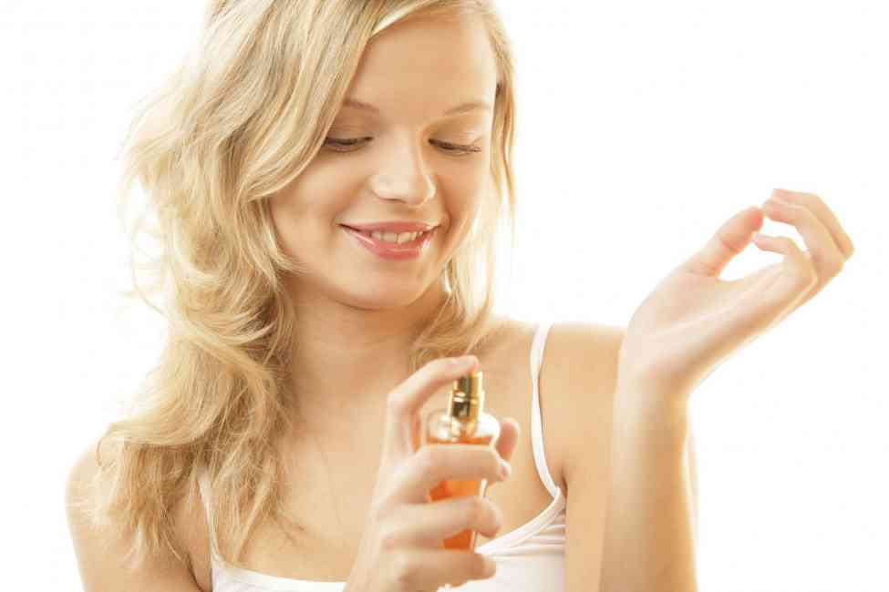 Blonde woman spritzing perfume on her wrist.