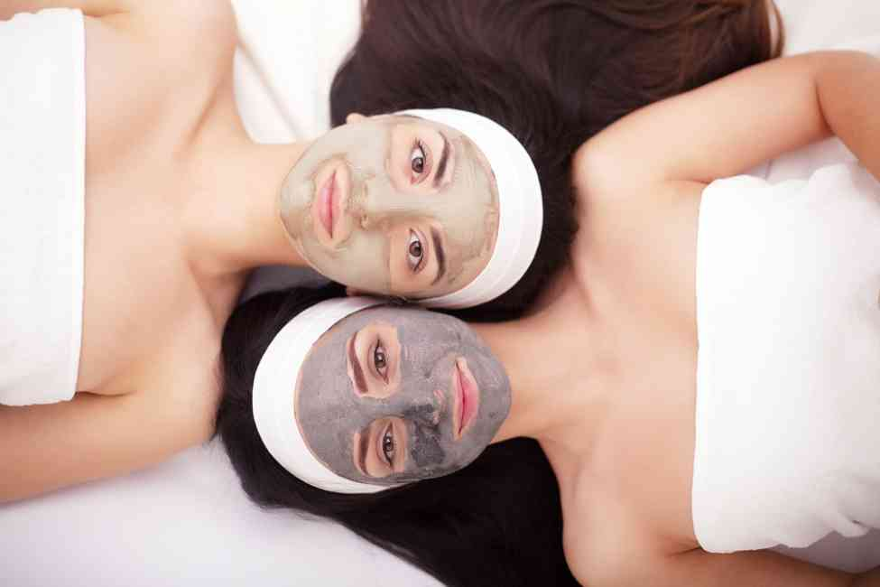 Two girls laying down with clay/mud masks on.
