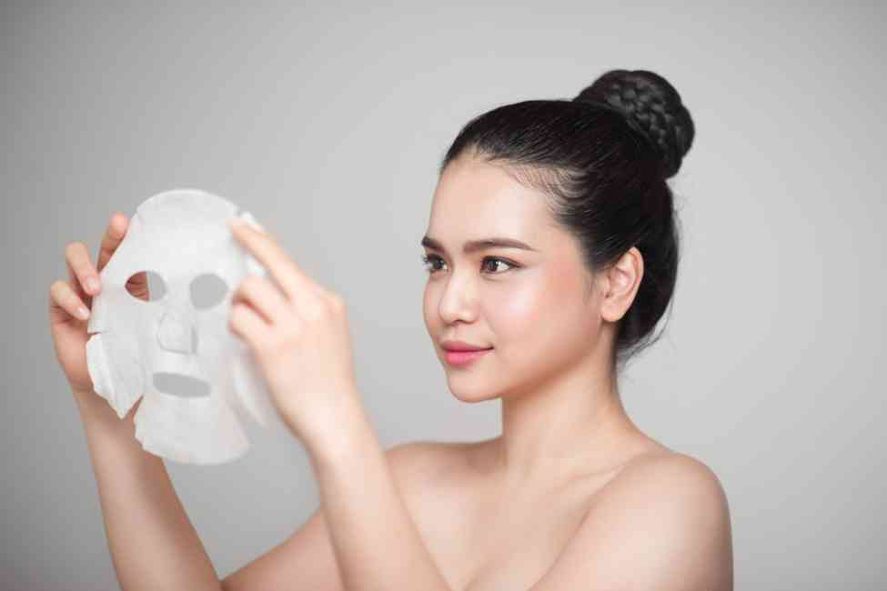 Woman holding a sheet mask in her hands prior to applying it to her face.