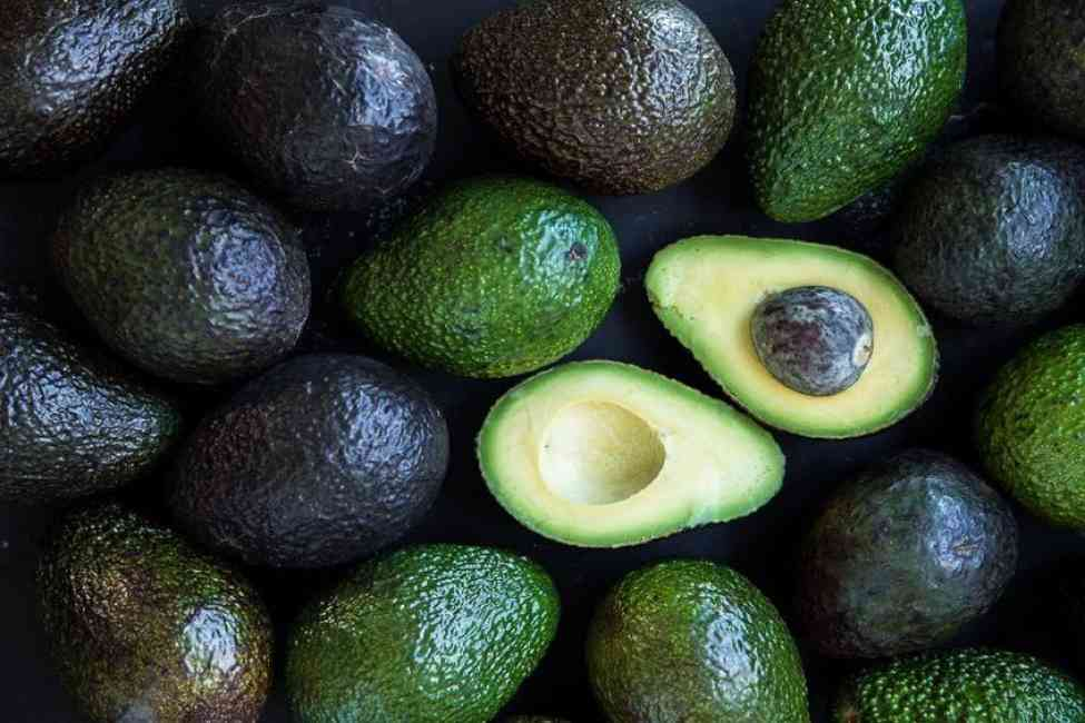 One sliced avocado among various other avocados, ripe and unripe.