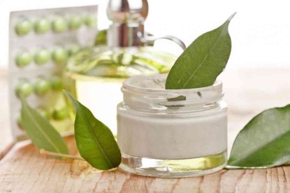 Tub of organic skincare lotion on a table surrounded by leaves. Blurred background features other organic skincare materials such as glass jar and vitamins.