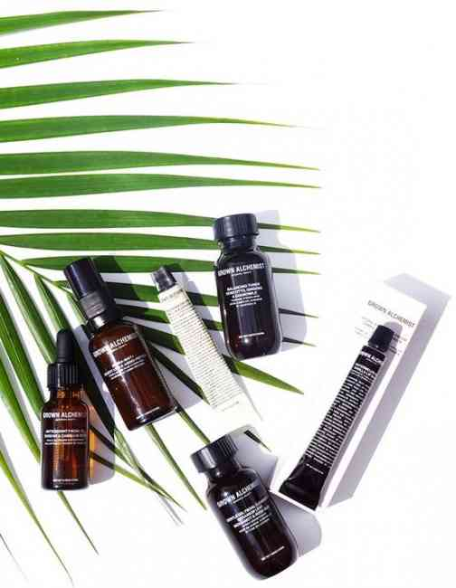 Six Grown Alchemist Skincare products flat-layed on a white background with a green tropical leaf.