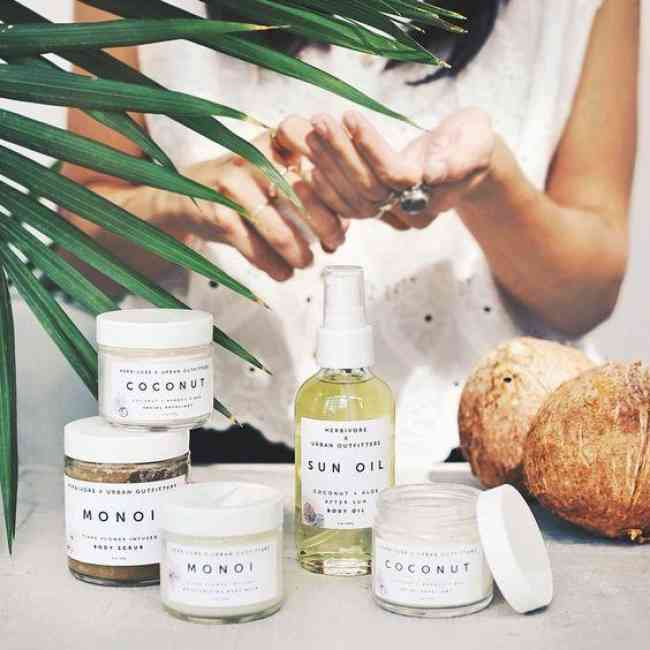 Female pictured applying exclusive Herbivore Botanicals x Urban Outfitters products to her hand. Five organic exclusive Herbivore Botanicals x Urban Outfitters products are shown along with a tropical plant and two coconuts.