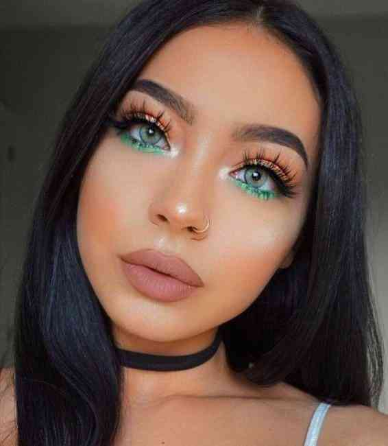 Beautiful girl adding to a pop of green colour to a neutral makeup look.
