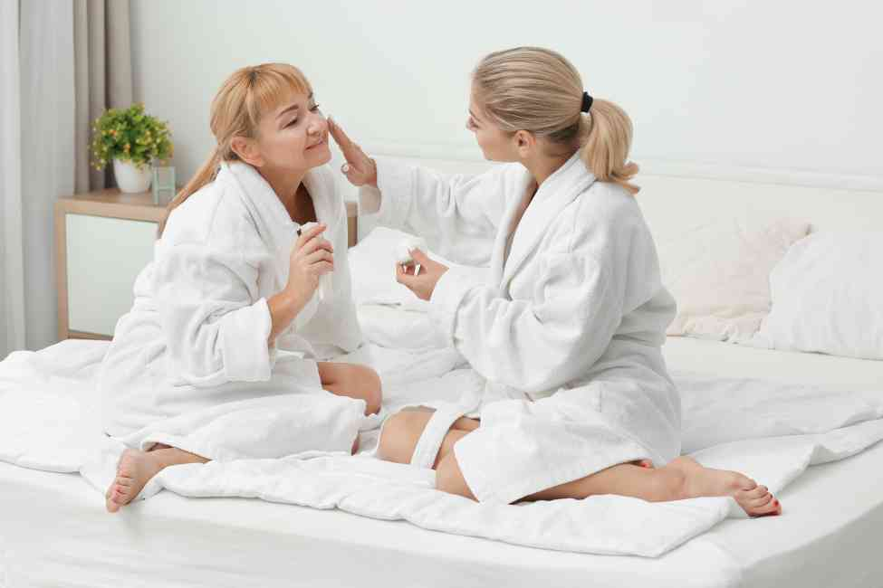 Daughter applying face cream to her mums skin