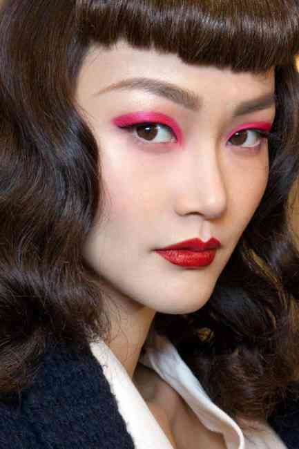 Model wears bright pink eyeshadow and a red lip by Pat McGrath.