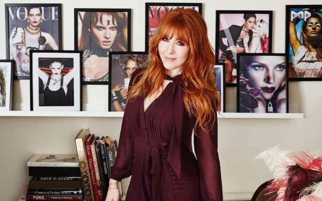 Portrait of makeup artist Charlotte Tilbury standing among many of her vogue magazine covers and photographs of models she has worked on