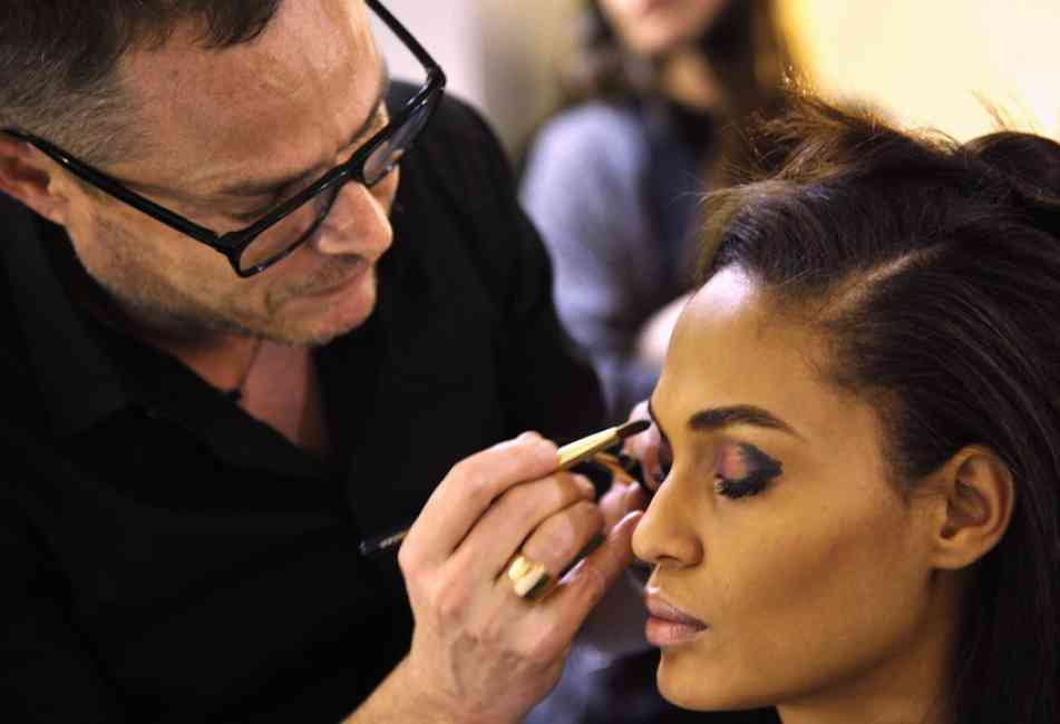 Tom Pecheux applying eye makeup to model backstage.