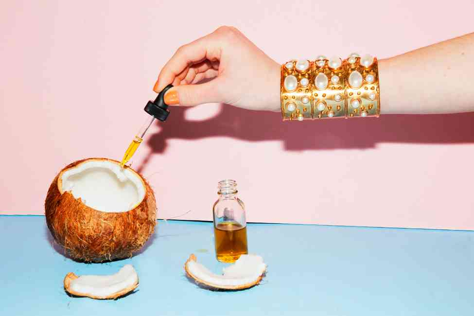 Coconut oil being extracted from a coconut by someone wearing a statement bracelet.