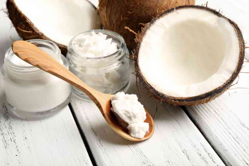 Coconuts, coconut oil in a jar and on a spoon