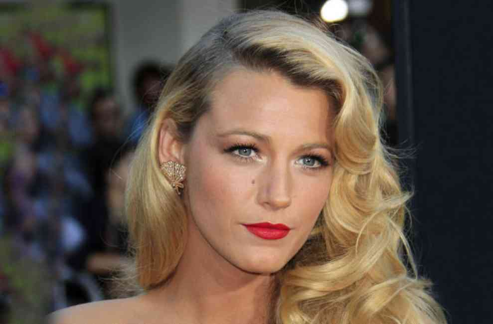 Blake Lively with side swept curls and bold red lip.