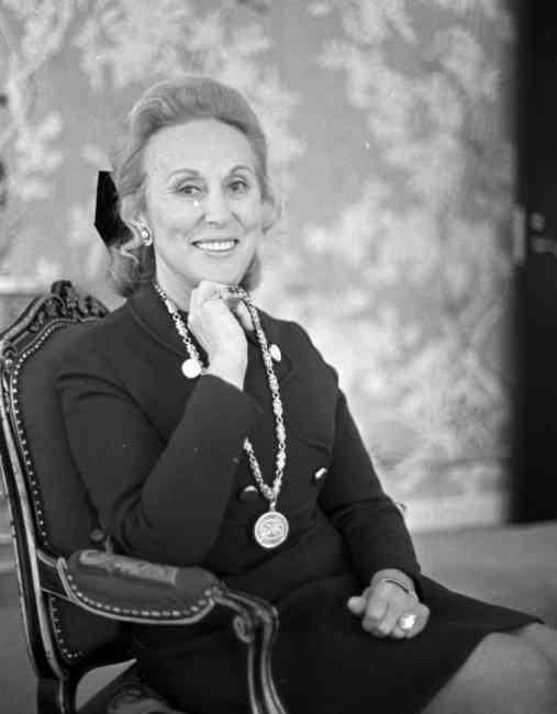 Black and white portrait photograph of Estée Lauder sitting on a chair posing.