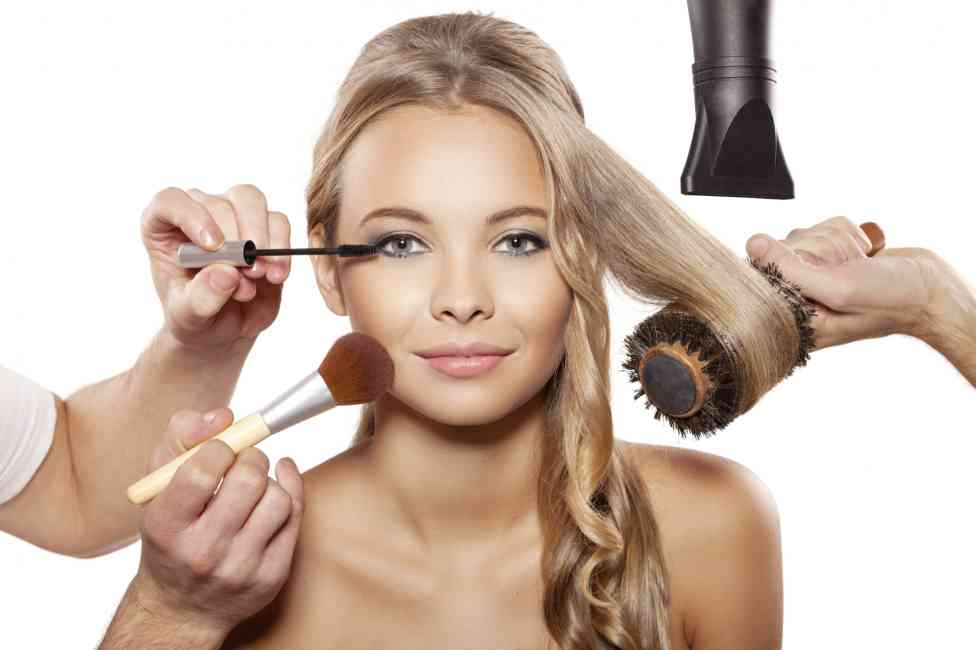 Blonde woman getting hair hair and makeup done by multiple hands. This details the concept of getting ready quickly, with both hair and makeup.
