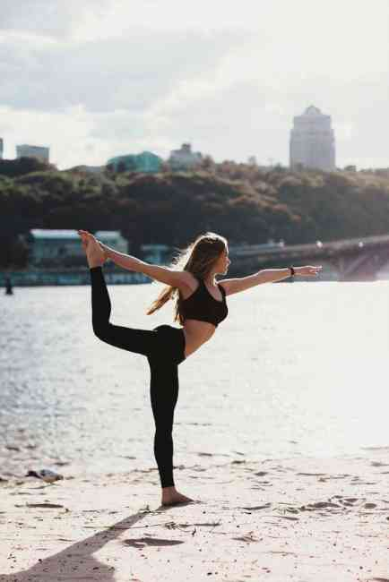 Woman doing a yoga position on the beach.