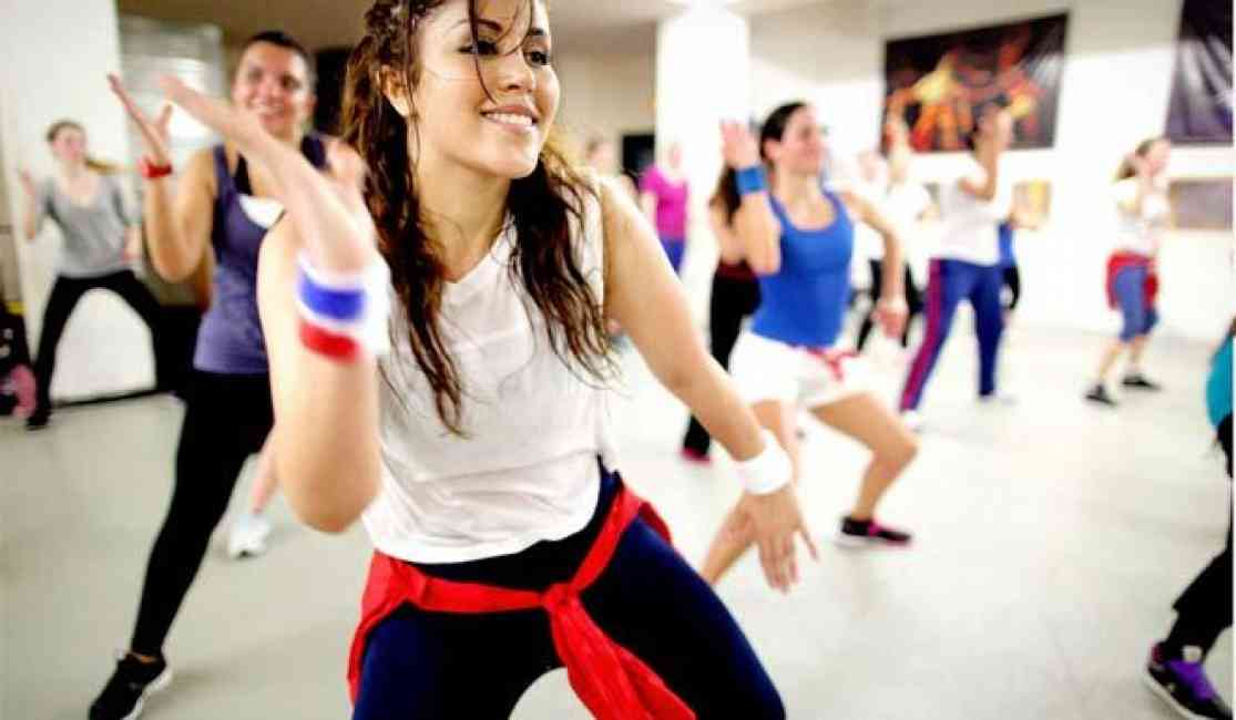 Woman dancing among others in a Zumba class.