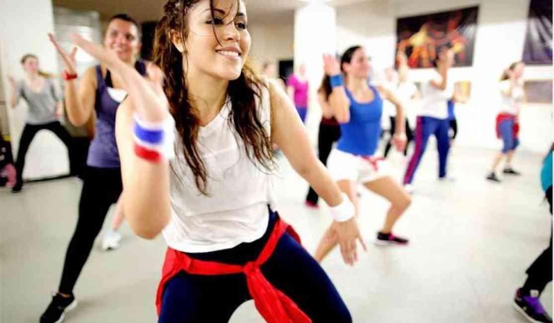 Woman dancing among others in a Zumba class.
