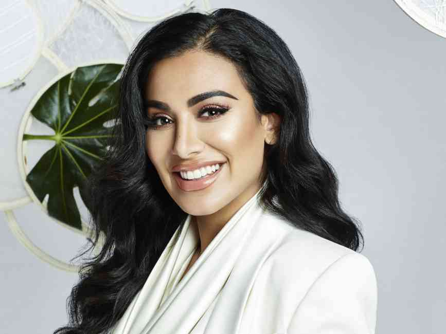 Portrait of Huda Kattan smiling.