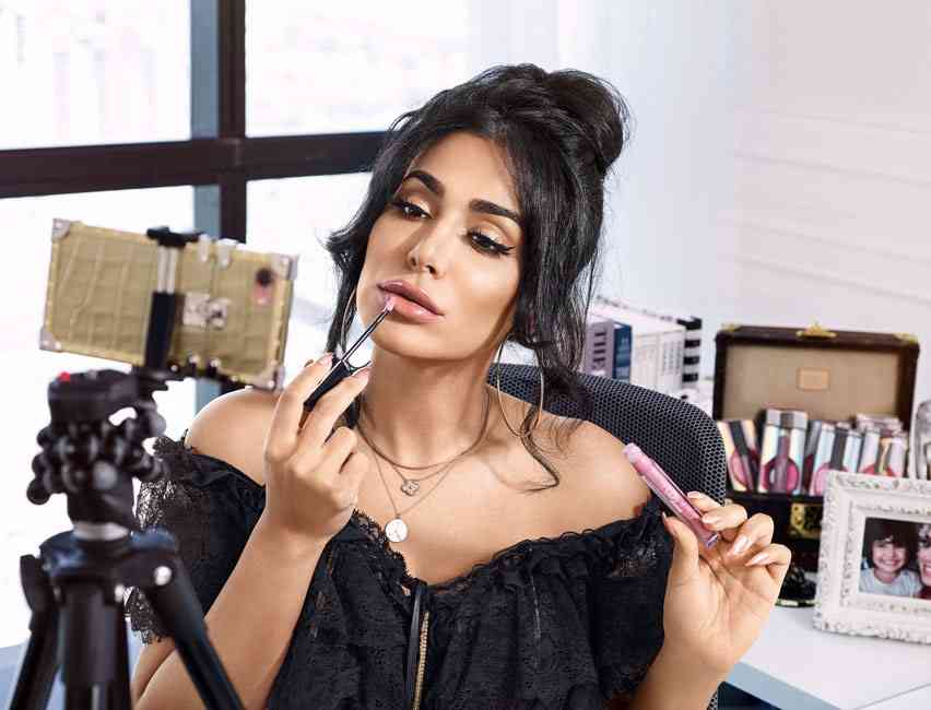Huda Kattan applying her own makeup line of Huda Beauty while filming content for social media on her phone.