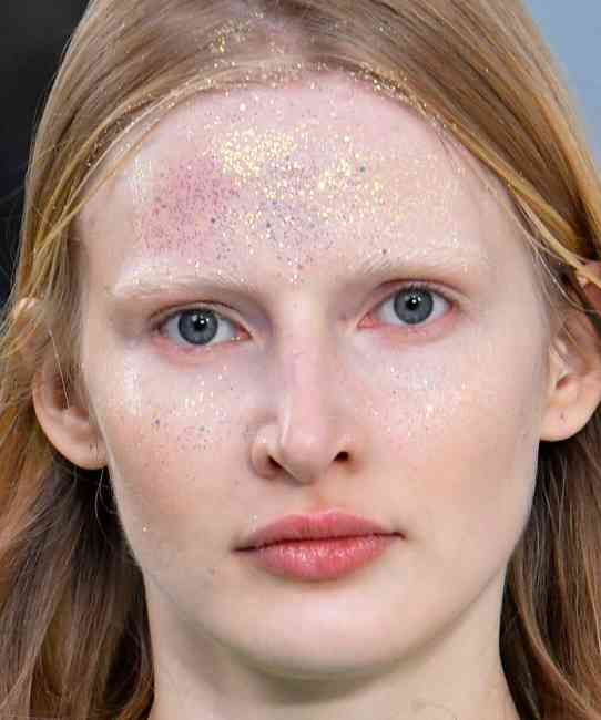Glitter lightly blown onto the models' foreheads.