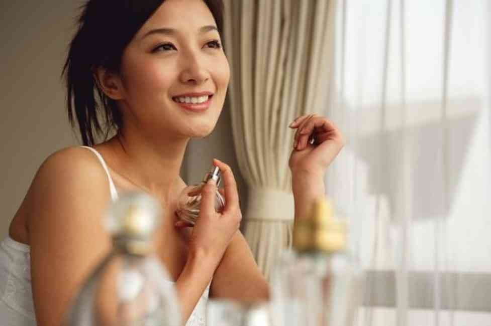 Young Asian woman sitting and smiling while spraying her neck with perfume.