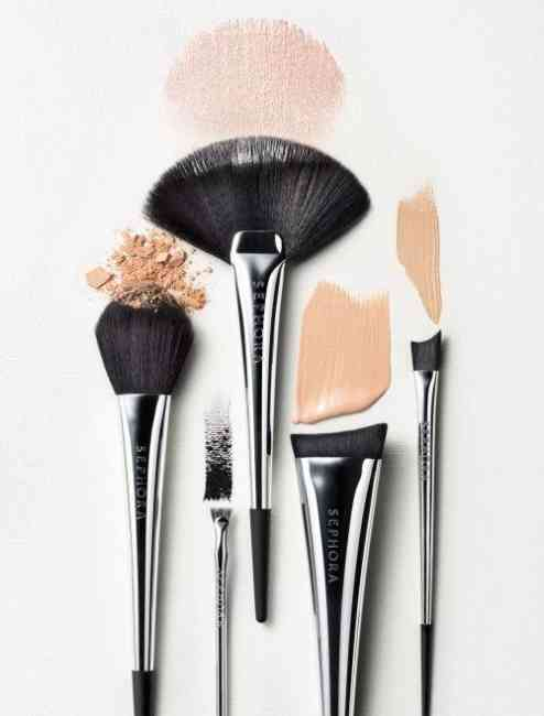 Blush brush, fan brush, small eye brush, angled foundation brush and angled concealer brush flat layed with swatches of different makeup products.