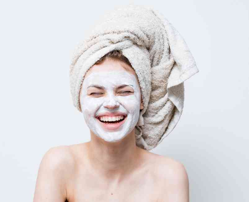 Woman with a mask on her face and hair wrapped in a towel smiling.