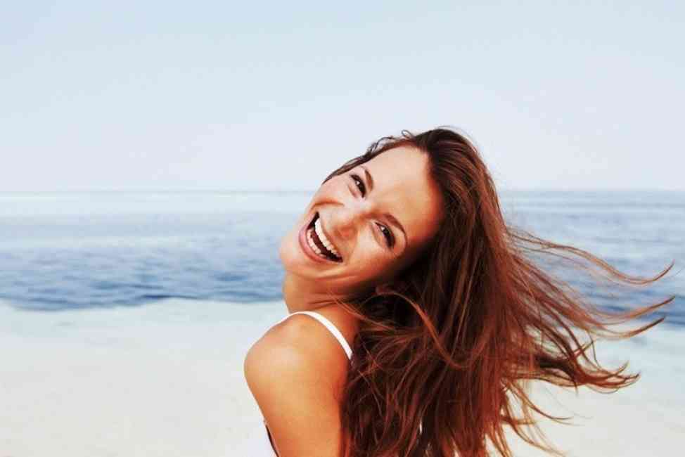 Woman pictured on the beach smiling, beaming with happiness.