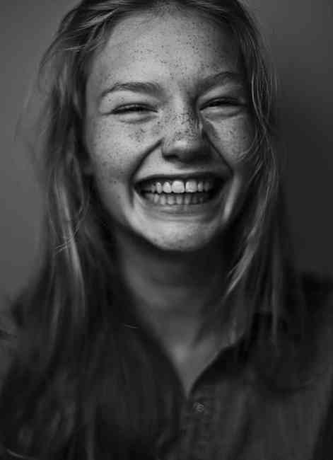 Black and white portrait of young girl with freckles smiling.