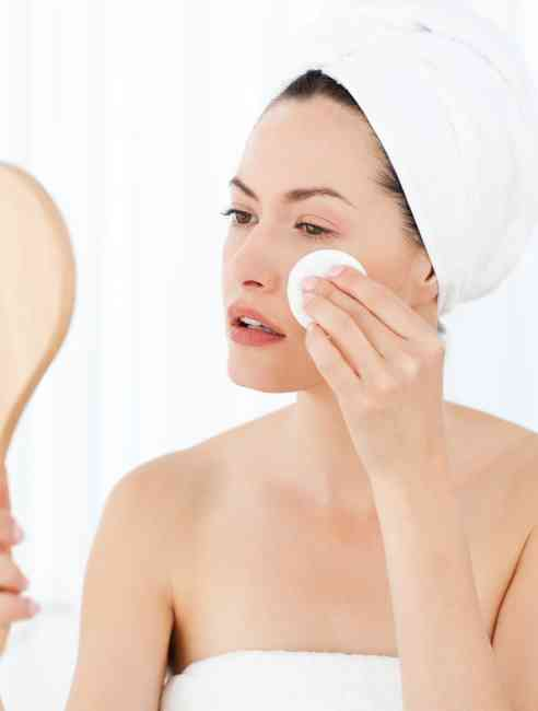Woman applying toner on a cotton pad to her face.