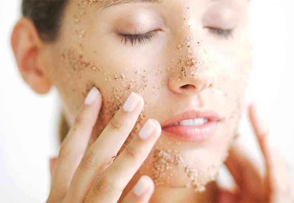Woman with eyes closed applying exfoliating scrub to her face with her hands