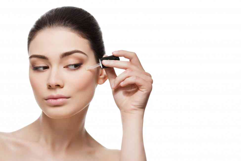 Woman applying serum to the under eye area.