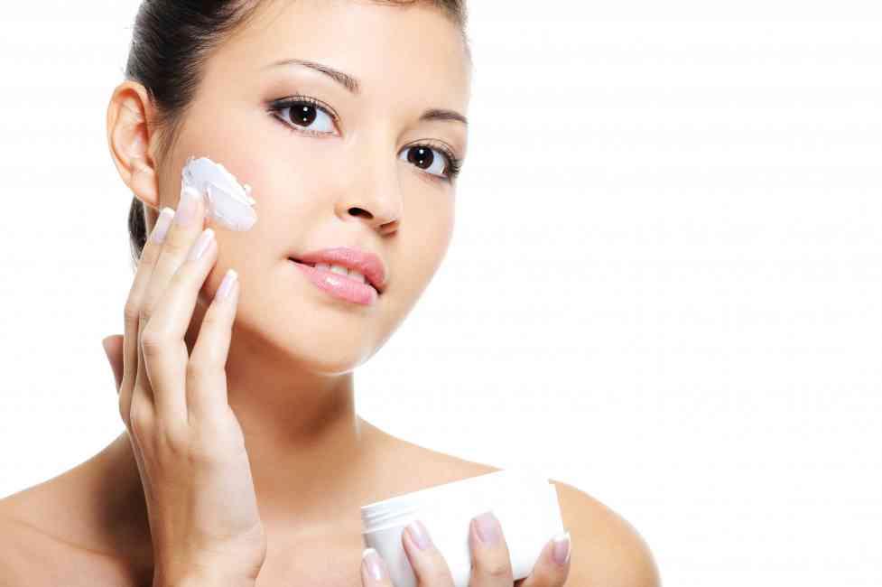 Woman applying moisturiser to her face.