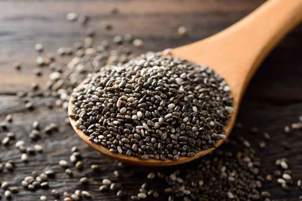 Image of black chia seeds in a wooden spoon.