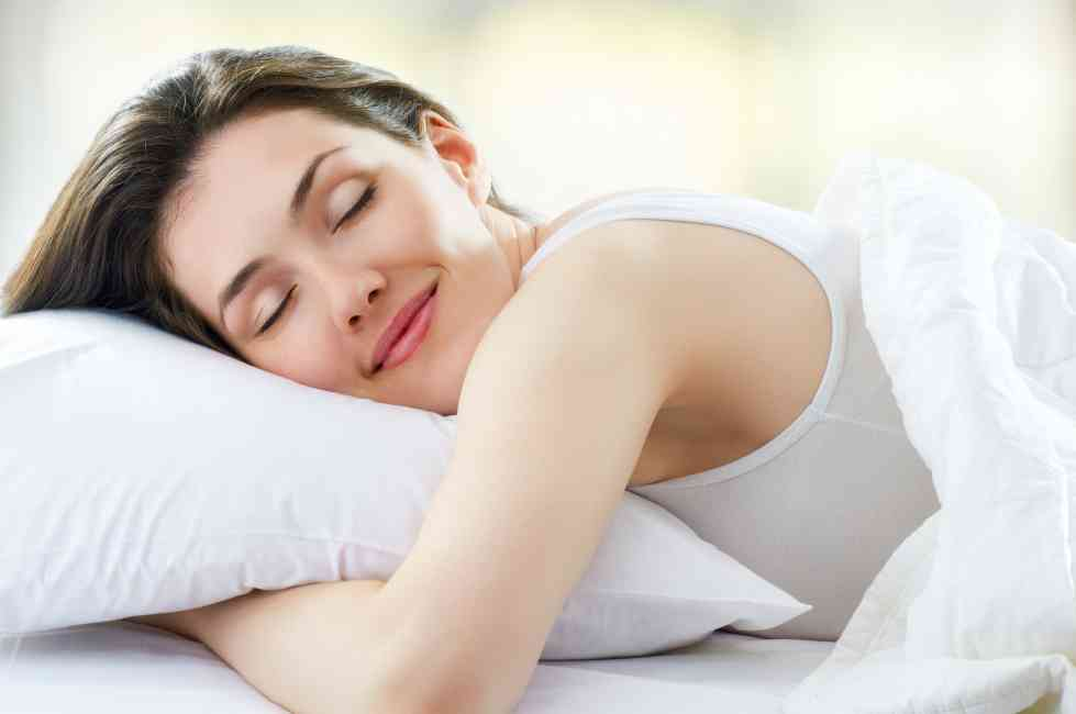 Picture of a woman happily sleeping in bed.