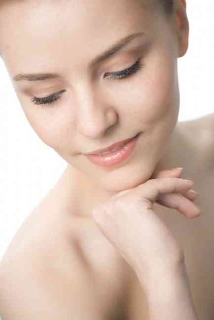 Image of a woman looking down with fabulous, clear skin.