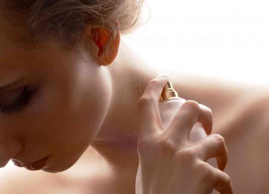 Customer spraying perfume on skin